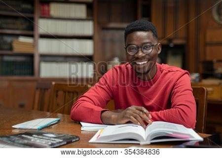 Portrait of university student doing homework in school library and smiling. Happy high school student looking at camera while studying for exam. African american guy with open book and copy space.