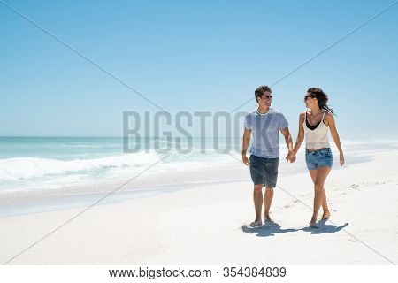 Happy young couple holding hands and walking barefoot on beach with copy space. Handsome man and beautiful woman in casual wearing sunglasses at seaside. Smiling couple relaxing on the sea shore.
