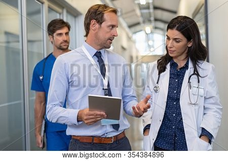Man and woman doctor having a discussion in hospital hallway. Doctor discussing patient case status with his medical staff after operation. Pharmaceutical representative showing medical report.