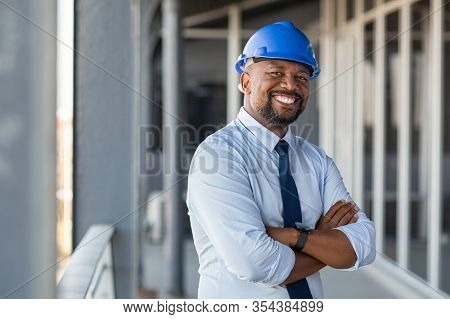 Portrait of african american man architect at building site looking at camera. Confident construction manager wearing hardhat. Successful mature civil engineer at construction site with copy space.