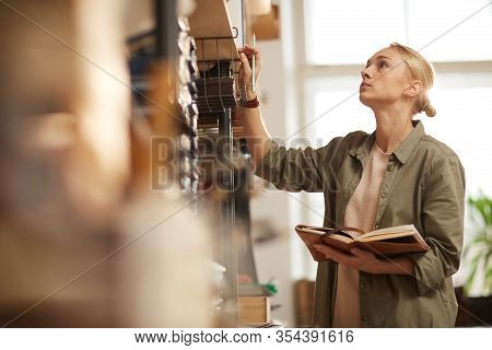 Young Female Artisan Holding Notebook Looking For Materials For New Craftwork, Horizontal Medium Sho