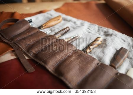 Horizontal High Angle Shot Of Of Tools For Craftwork In Handmade Case And Piece Of Leather Material