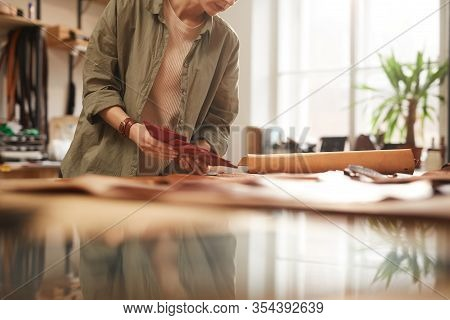 Horizontal Shot Of Unrecognizable Female Artisan Attentively Choosing Material For Her New Craftwork