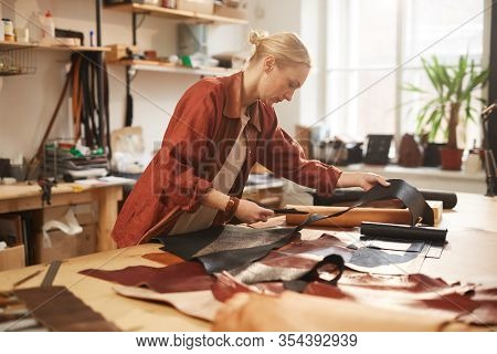 Young Adult Blond Woman In Casual Outfit Standing At Table In Her Workshop Cutting Out Leather For N
