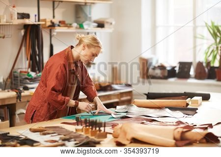Horizontal Side View Portrait Of Modern Female Artisan Doing Leather Craftwork Standing At Table In