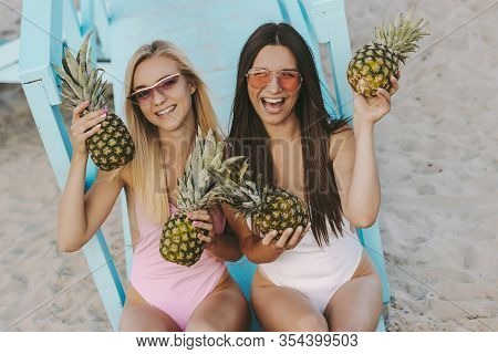Cheerful Young Women Friends Holding Pineapples In Hands And Laughing While Sitting On Lifeguard Tow