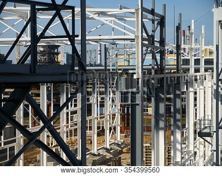Work Site And Large Steel Frame Of A Large Commercial Building Over Petrochemical Plant Landscape.