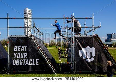 Malmö, Sweden May 11, 2019: Two Men Are Making A Big Jump On An Obstacle Which Is Part Of The Race T