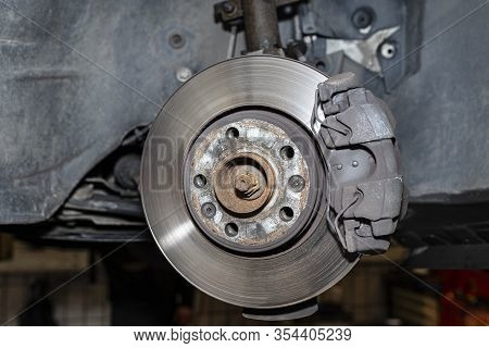 Front Brake Discs With Brake Caliper And Brake Pads In The Car, On A Car Lift In A Workshop.