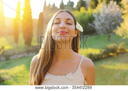 Portrait Of Young Smiling Woman With Closed Eyes And Flower On Ear Taking Deep Breathing. Positive S