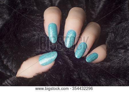 Female Hand With Glittered White Blue Nails Is Holding Black Fur, Manicure And Nail Care Concept.