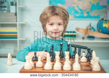 Chess Strategy. Kid Playing Chess. Child And Childhood. Clever Concentrated And Thinking Child While