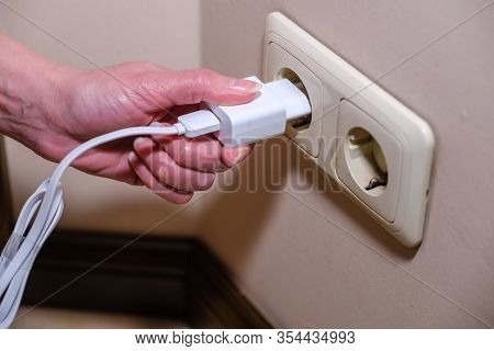 Close-up Woman Hand Puts Plug In The Electricity Socket. Female Hand Unplugging