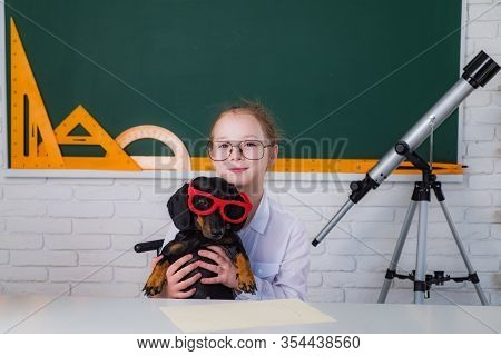 Funny Portrait Clever Pupil Girl Hold Funny Pet Dog On School Board Background. Funny Smiling Little
