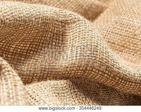 Crumpled Brown Sackcloth, An Abstract Background. Close Up View On Brown Burlap Textile. Texture Of