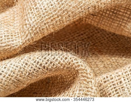 Close Up View On Brown Crumpled Sackcloth. Abstract Background Of Burlap Textile. Texture Of Brown B
