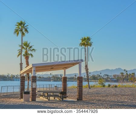 Barbecue And Picnic Table Under A Shade Canopy And Palm Trees In Rotary Community Park, Lake Havasu,