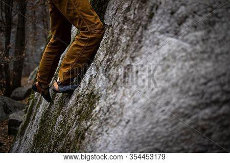 A rock climber climbing on a boulder rock outdoors.