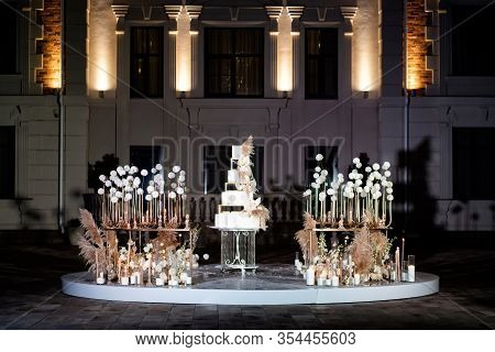 Photo Zone With Unusual White Tiered Wedding Cake. Wedding Decor. A Traditional Treat For The Feast