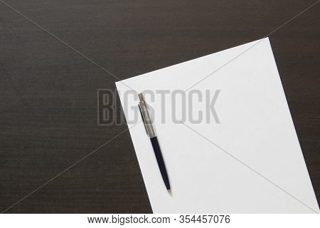 Template Of White Paper With Pen On Dark Wenge Color Wooden Background. Concept Of Business Plan And