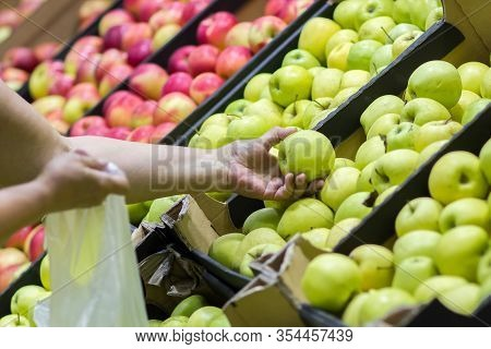 Old Woman Selecting Fresh Apples In Grocery Store Produce Department And Putting It In Plastic Bag.