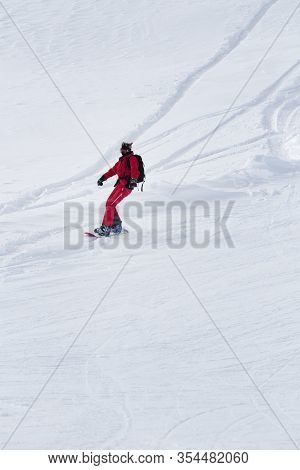 Snowboarder In Red Descends On Snowy Ski Slope At Gray Winter Day