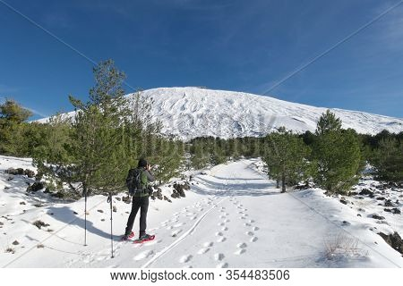 snow covered path to Etna Mount, hiker with snowshoes take a picture, Sicily