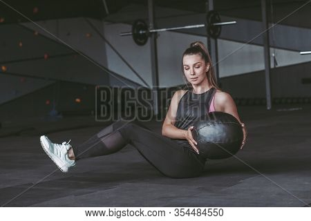 Beautiful Young Sports Woman Doing Abs Exercises With Medicine Ball While Sitting On Floor In Dark G