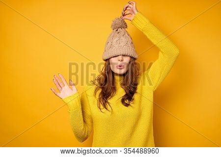 A Brunette In A Yellow Sweater Stands On A Yellow Background With A Cap Pulled Over Her Face And Pul