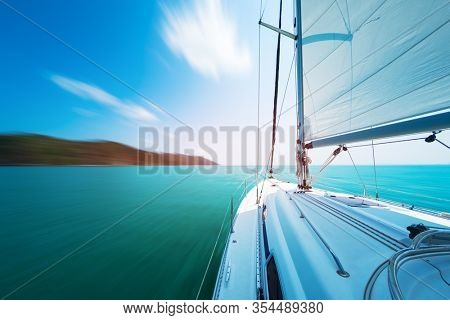 Sailing yacht moves in the sea under the main sail. Image is mottion blurred