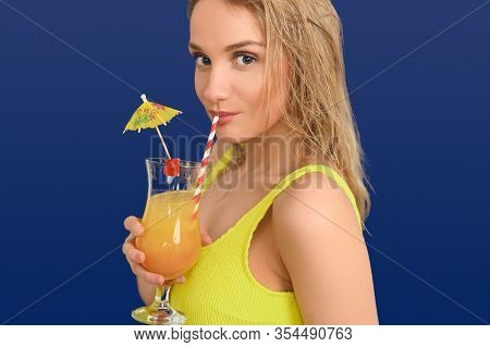 Young Attractive Blond Woman In Yellow Sleeveless Summer Top Sipping An Exotic Fruit Cocktail On Sum