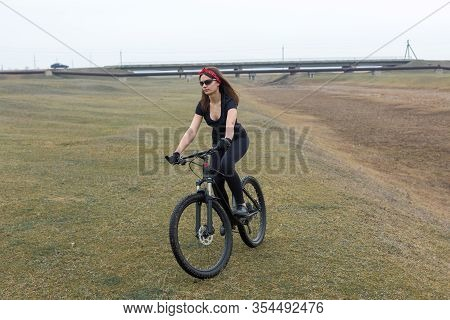Girl On A Mountain Bike On Offroad, Beautiful Portrait Of A Cyclist At Sunset, Fitness Girl Rides A