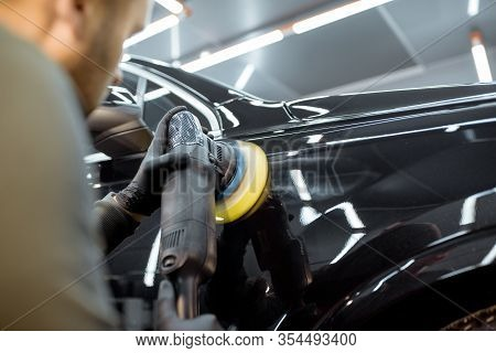 Worker Polishing Vehicle Body With Special Grinder And Wax From Scratches At The Car Service Station