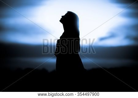 Youth Woman Soul At Blue Sun Meditation Dreaming Past Times. Silhouette In Front Of Sunset Or Sunris
