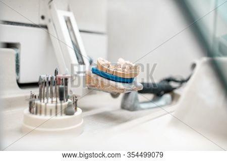 Artificial Jaw For Implants Modeling With Set Of Dental Burs At The Working Place Of Dental Technici