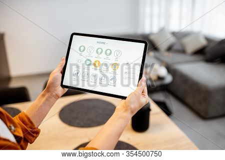 Young Woman Controlling Home With A Digital Touch Screen Panel. Concept Of A Smart Home And Mobile A