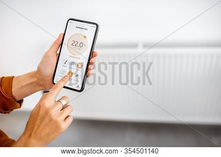 Controlling Radiator Heating Temperature With A Smart Phone, Close-up With Radiator On The Backgroun