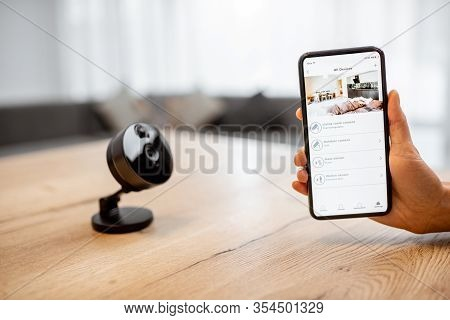 Close-up On A Smart Phone With Launched Security Application And Ip Camera At The Table. Home Video