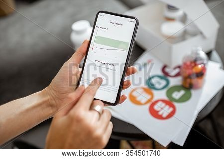 Woman Checking The Result Of Medical Tests On A Smartphone, Close-up With Nutritional Supplements On