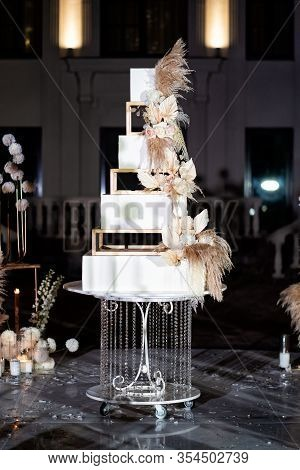 Unusual White Square Tiered Wedding Cake With Feathers. A Traditional Treat For The Feast Of The Bri