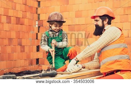 Building Tools. A Smiling Builder In A Hard Hat Buiding A Brick Wall. Worker Installing Red Brick Fo