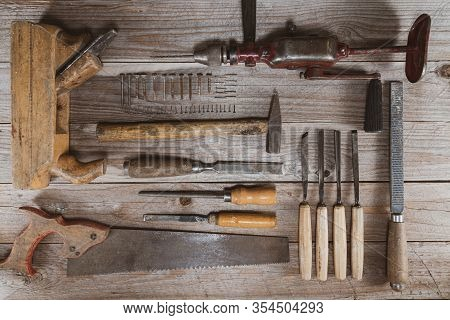 Vintage Woodworking Tools On A Wooden Background. Chisels, Rasps, Plane, Hand Drill, Saw, Screws And