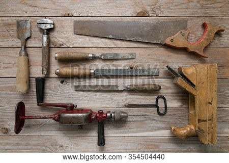 Vintage Woodworking Tools On A Wooden Background. Chisels, Rasps, Plane, Puncher And A Hand Drill Ne