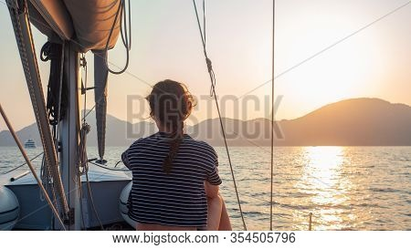 Attractive Young Woman In A Striped T-shirt Enjoys The Sunset On The Deck Of A Sailing Yacht. Sailor