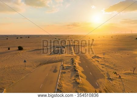 Aerial View Of Half Desert Road Or Street With Sand Dune In Dubai City, United Arab Emirates Or Uae.