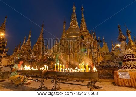 Yangon, Myanmar - December 19, 2019: A Woman Light Candle In Front Of Shwedagon Pagoda At Dusk. Shwe