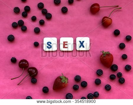 Pink Background Covered With Berries And Fruit. Copy Sex - Word Spelled With Letter Pieces On Pink B