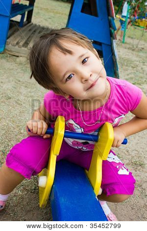 Happy, Little Girl Playing On The Playground