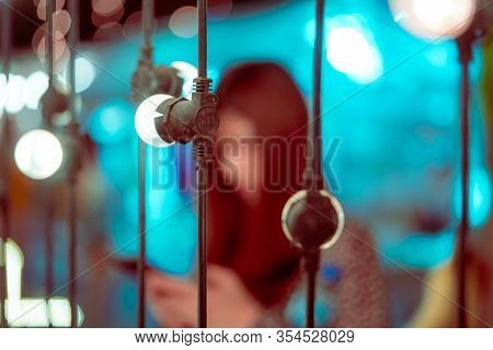 Blurred Picture Of A Woman On Bright Bokeh Light On Chair Decoration In Outdoor Festive Market In Lu
