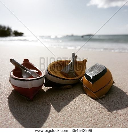 This Is A Photograph Of Miniature Boats On The Sand Of A Tropical Beach